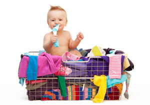 Happy toddler sitting  in basket with clothes