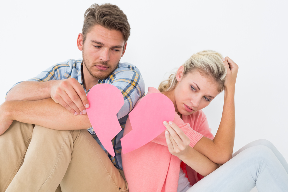 Young couple holding two halves of broken heart over white background